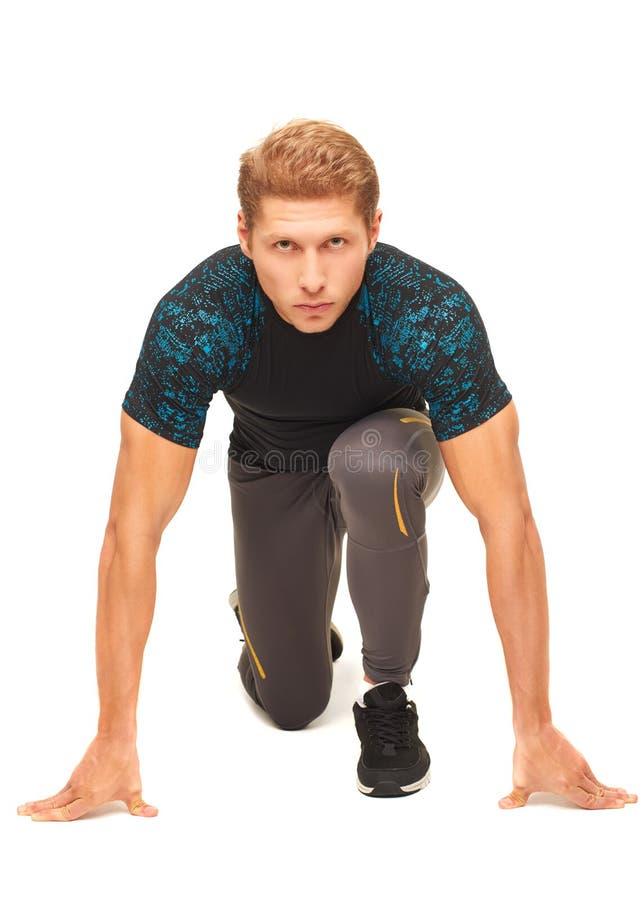 Ung muskulös stilig idrottsman som förbereder sig att starta köra arkivfoton