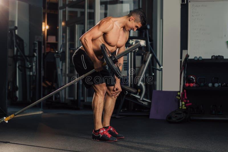 Ung muskul?s man i idrottshallen som g?r ?vning arkivfoto