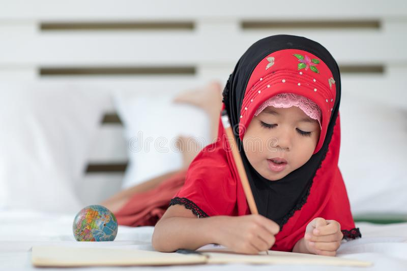Ung muslim flicka som skriver en bok, islamiskt barn för att göra läxa hemma royaltyfria bilder