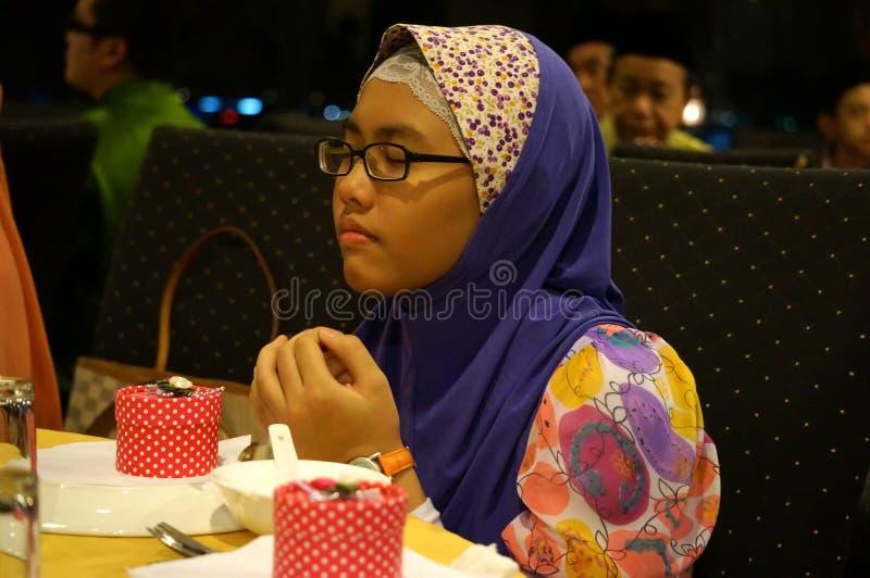 Ung muslimflicka som ber, isolerat på grå bakgrund royaltyfri fotografi