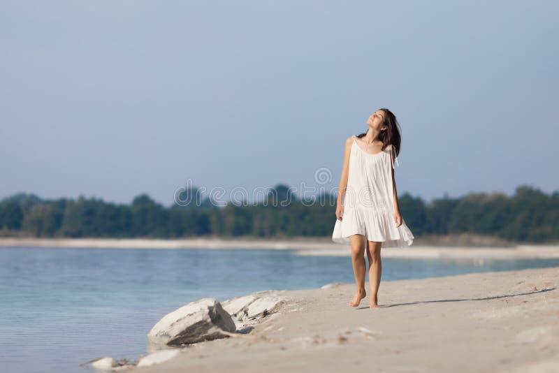 Ung mycket härlig flicka med långt hår i en vit klänning vid sjön royaltyfria bilder