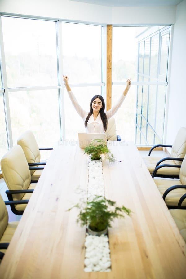 Ung nätt affärskvinna i kontoret som i regeringsställning sitter stol, händer upp och med hennes fot upp på ett skrivbord royaltyfri bild