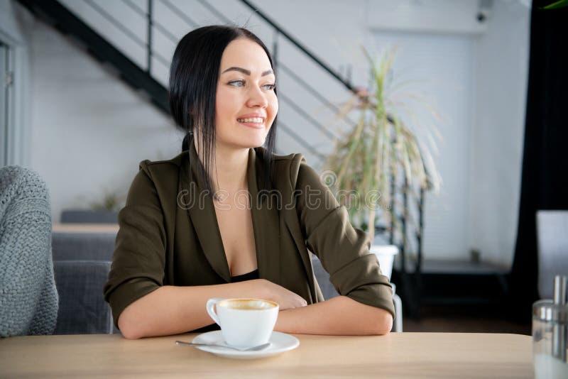 Ung nätt affärskvinna som i regeringsställning dricker kaffe, bredvid exponeringsglasfönstret royaltyfri fotografi