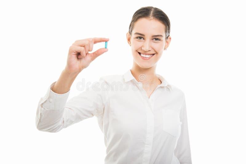Ung nätt affärskvinna som visar ett blått piller royaltyfria foton