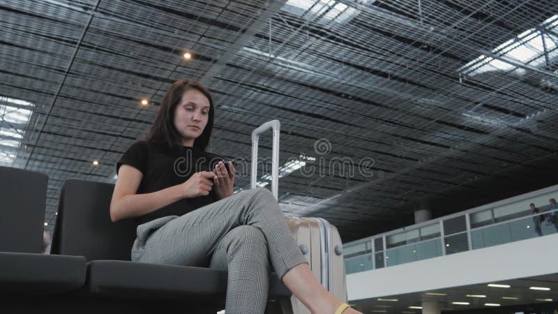 Ung nätt affärskvinna Using en Smartphone på flygplatsen, medan vänta hennes kö för registreringen, resande begrepp royaltyfria foton