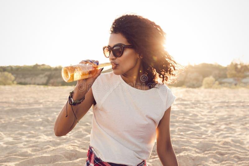 Ung nätt afrikansk flicka i solglasögon som dricker öl royaltyfria foton