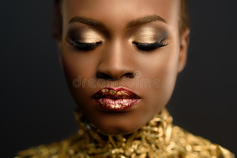 Ung nätt afrikansk kvinna, med hår som samlas i frisyren och det känsliga guld- sminket som poserar på svart bakgrund, i studio,  royaltyfria bilder