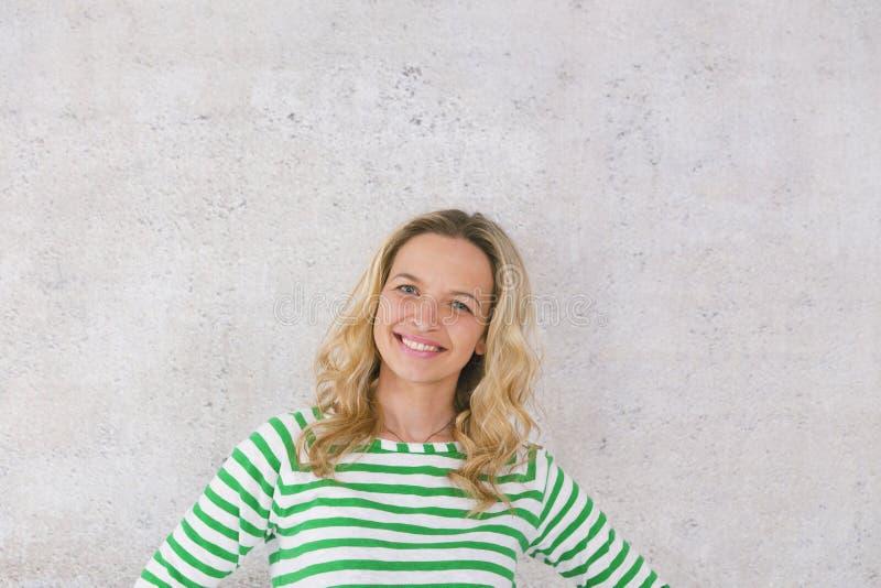 Ung nätt blond kvinna som framme poserar av en betongvägg och bär gröna vita randiga tröjor royaltyfri bild
