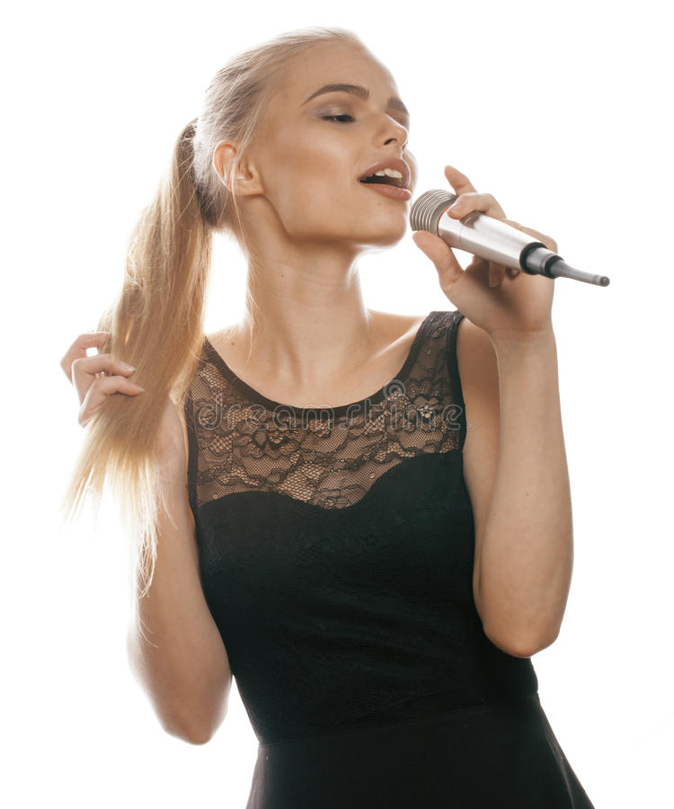 Ung nätt blond kvinna som sjunger i mikrofonen som tätt isoleras upp den svarta klänningen, karaokeflicka royaltyfri fotografi
