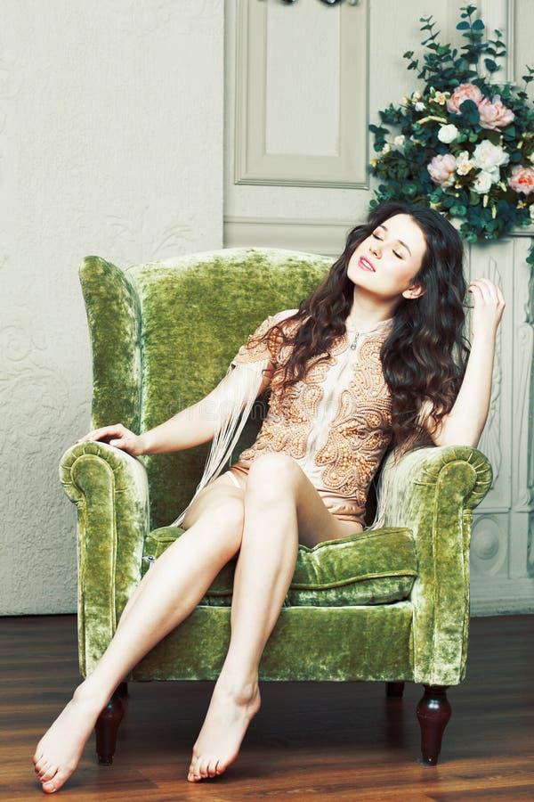 Ung nätt brunettflicka i modeklänning på soffan som poserar i lu royaltyfri fotografi