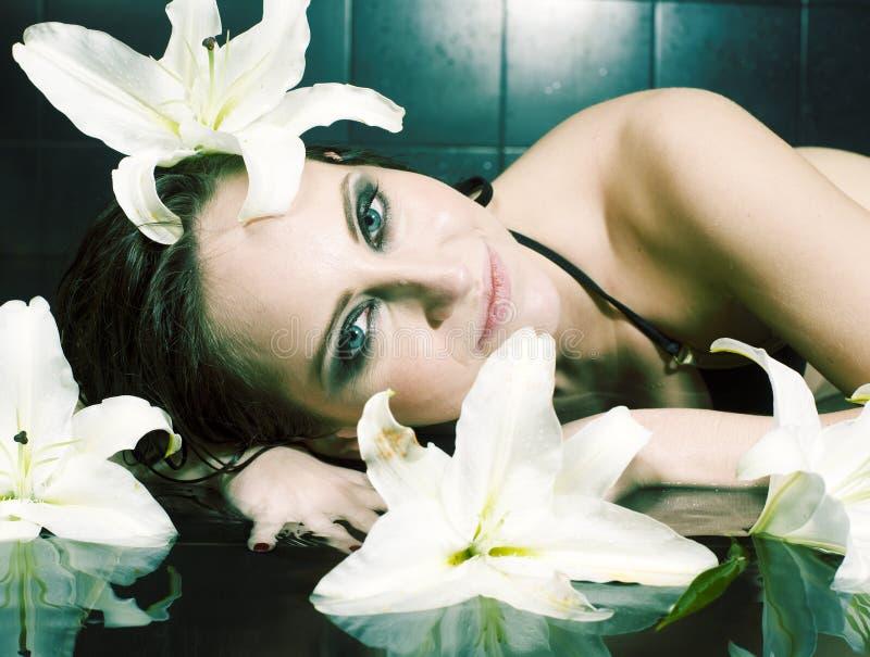 Ung nätt brunettkvinna i det svarta badet som tar brunnsortomsorg som poserar med liljan för vit blomma royaltyfri fotografi