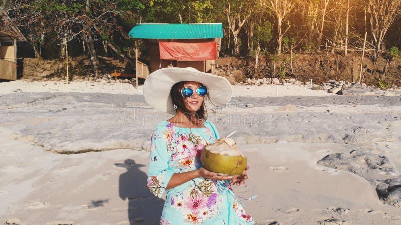Ung nätt brunettkvinna som kopplar av med kokosnötvatten på havstranden under blå himmel i solig dag arkivfoton