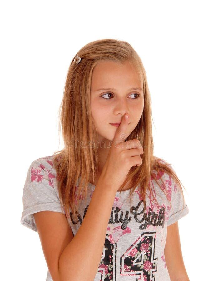 Ung nätt flicka med fingret över mun royaltyfria foton