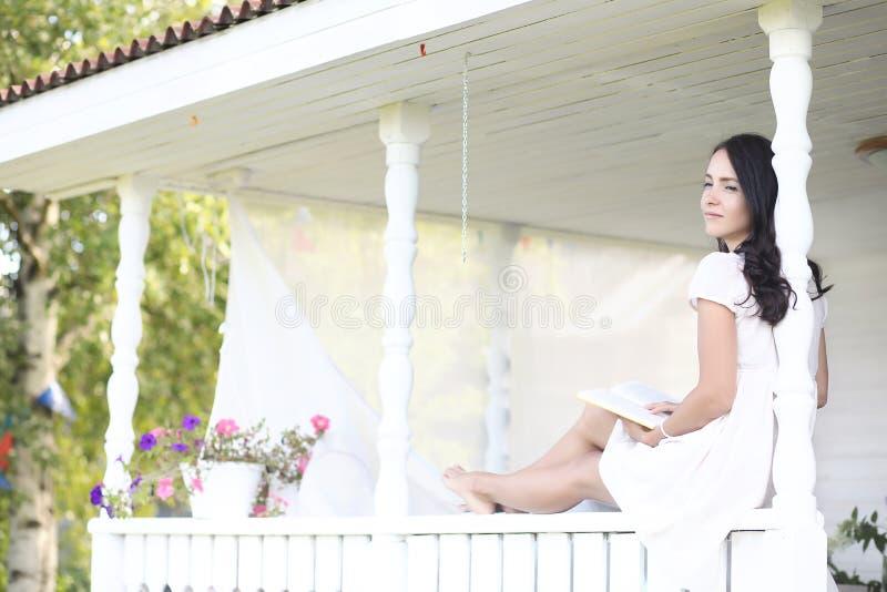 Ung nätt flicka med långt brunetthår i tappningsvartklänning i vita ärtor som sitter nära trähus i by royaltyfria bilder