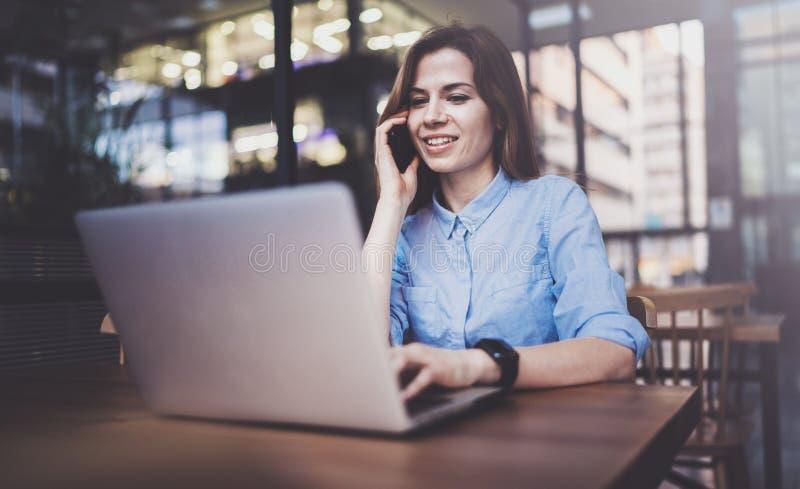 Ung nätt flicka som arbetar på bärbara datorn och använder den mobila smartphonen på hennes arbetsplats på den moderna kontorsmit arkivfoton