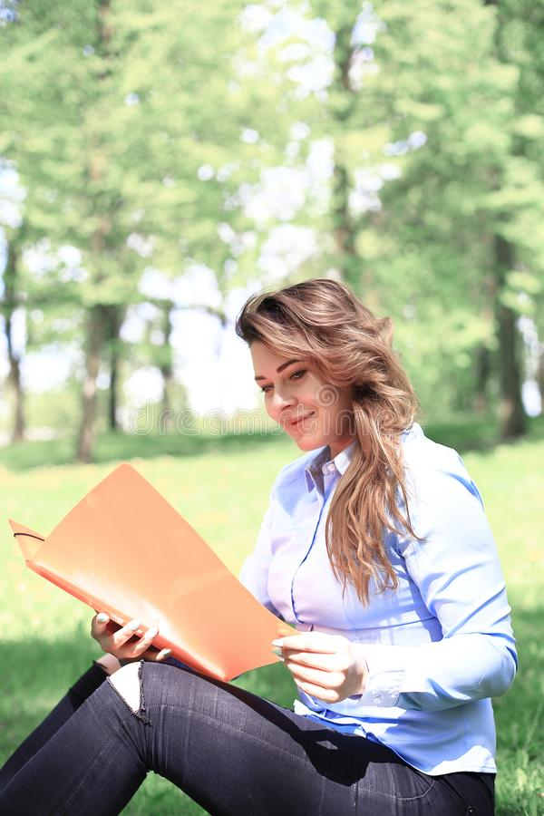 Ung nätt flicka som arbetar på den utomhus- bärbara datorn och att ligga på gräs, caucasian 20 gamla år fotografering för bildbyråer
