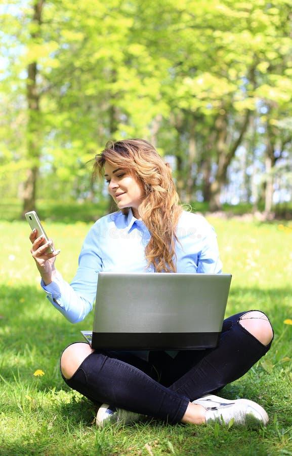 Ung nätt flicka som arbetar på den utomhus- bärbara datorn och att ligga på gräs, caucasian 20 gamla år royaltyfri bild