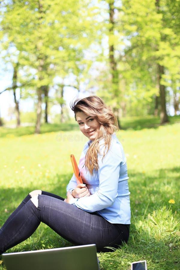 Ung nätt flicka som arbetar på den utomhus- bärbara datorn och att ligga på gräs, caucasian 20 gamla år royaltyfri fotografi