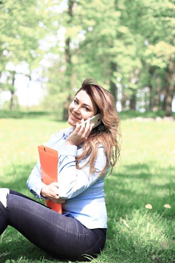 Ung nätt flicka som arbetar på den utomhus- bärbara datorn och att ligga på gräs, caucasian 20 gamla år arkivbilder