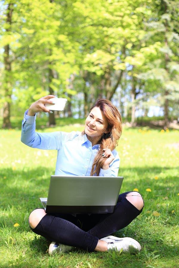 Ung nätt flicka som arbetar på den utomhus- bärbara datorn och att ligga på gräs, caucasian 20 gamla år royaltyfria bilder