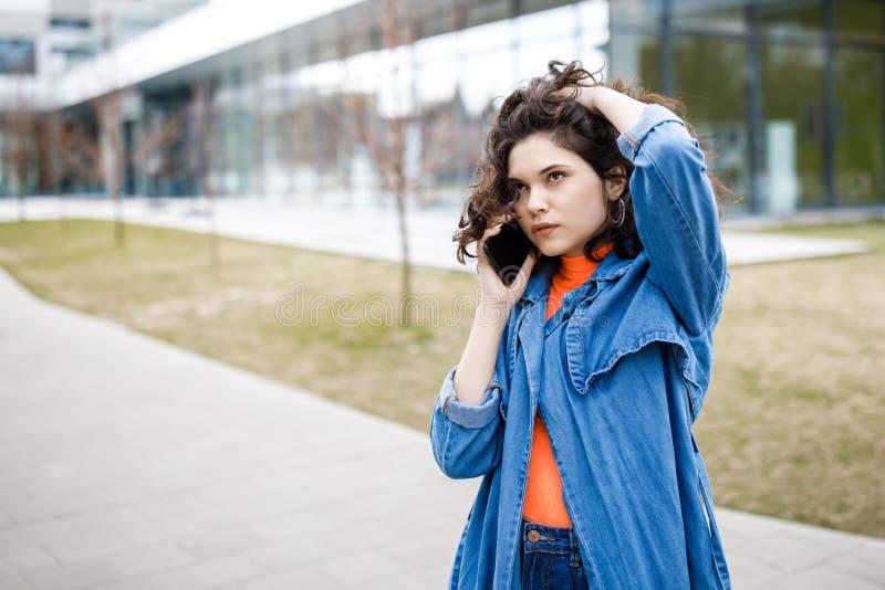 Ung nätt flicka som går på gatan, den iklädda jeansen och grov bomullstvillskjortan Studentvardagar Flickan talar på gatan på royaltyfri foto