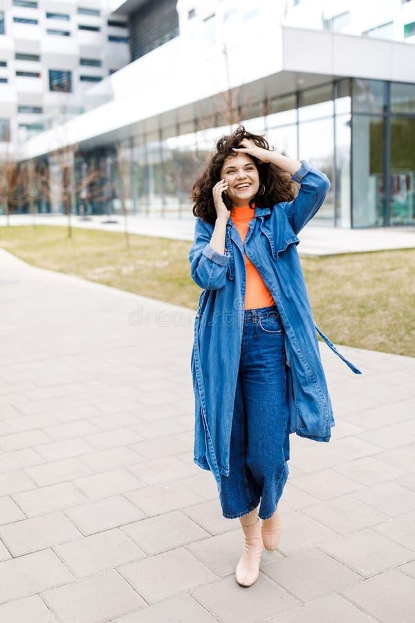 Ung nätt flicka som går på gatan, den iklädda jeansen och grov bomullstvillskjortan Studentvardagar Flickan talar på gatan på arkivfoton
