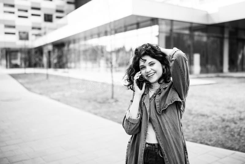 Ung nätt flicka som går på gatan, den iklädda jeansen och grov bomullstvillskjortan Studentvardagar Flickan talar på gatan på arkivbild