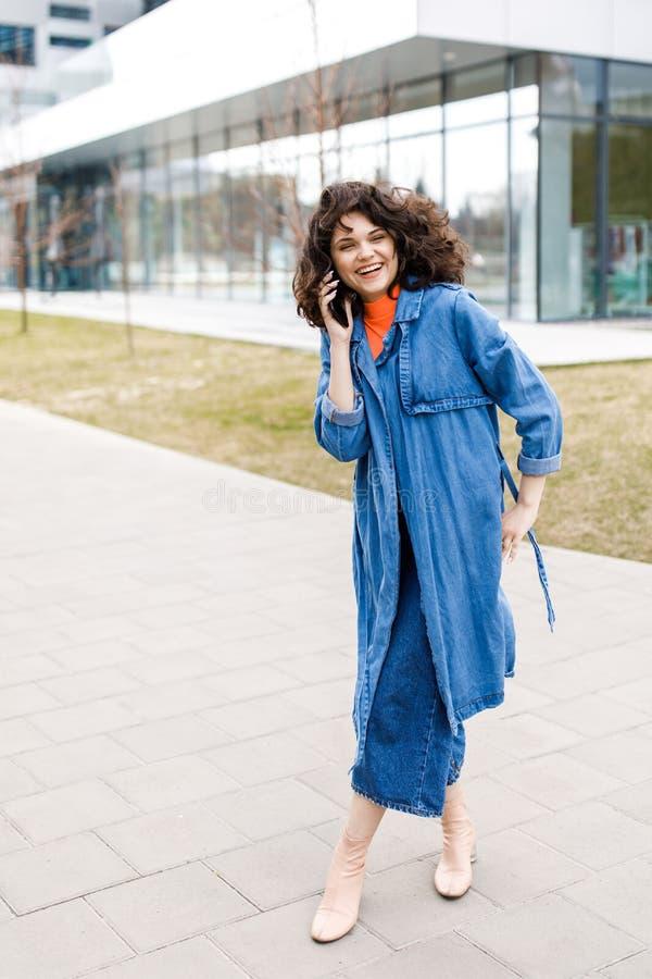Ung nätt flicka som går på gatan, den iklädda jeansen och grov bomullstvillskjortan Studentvardagar Flickan talar på gatan på royaltyfria foton