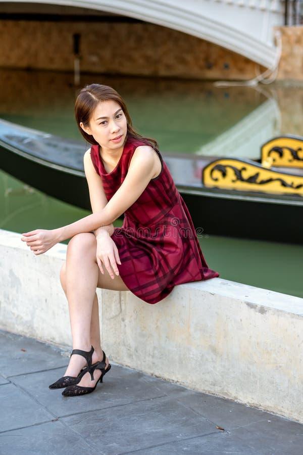 Ung nätt flicka som poserar på gatan på den soliga dagen arkivfoto