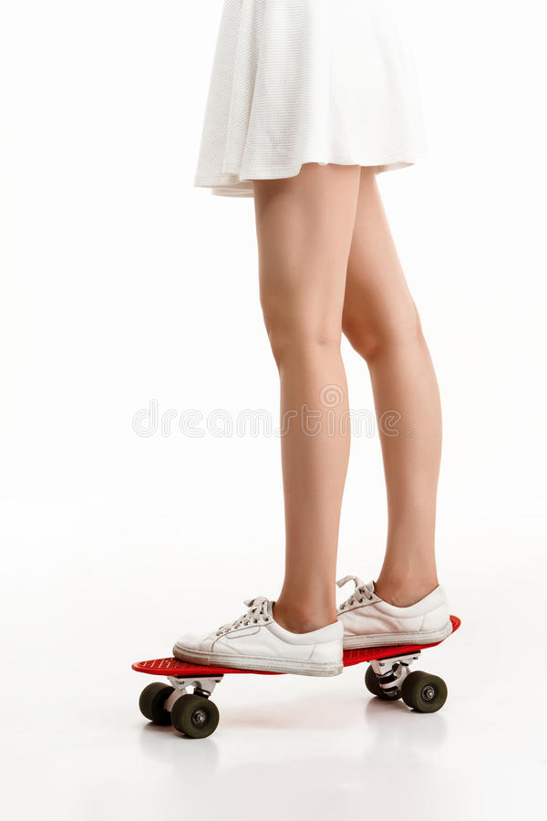 Ung nätt flicka som skateboarding över vit bakgrund close upp royaltyfri bild