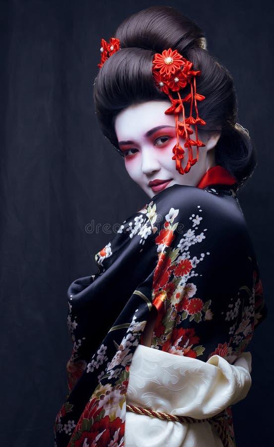 Ung nätt geisha i kimono med sakura och royaltyfri fotografi