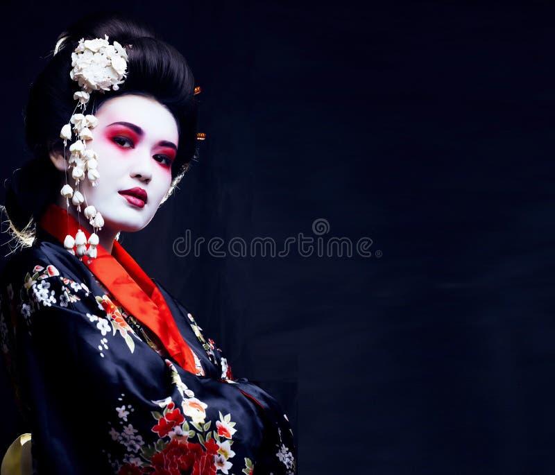 Ung nätt geisha i kimono med sakura och garnering fotografering för bildbyråer