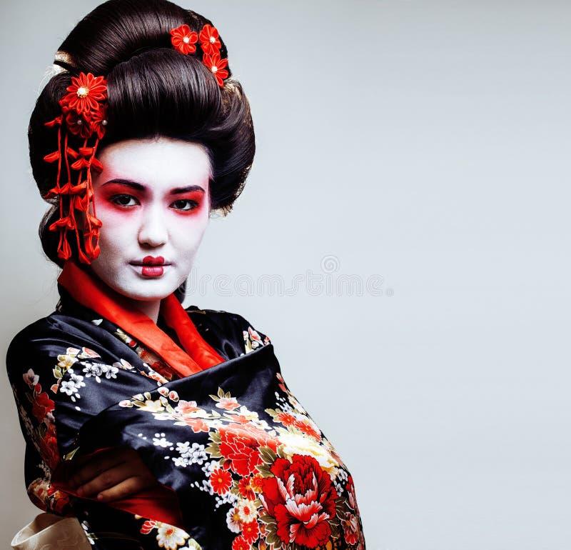 Ung nätt geisha i kimono med sakura och röd garneringdes arkivbilder