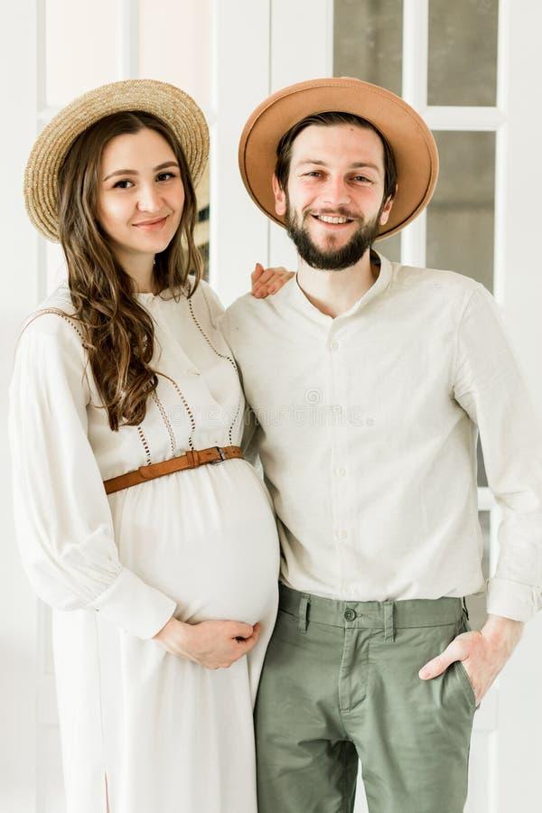 Ung nätt gravid kvinna och hennes make i hattanseende nära kaktusväggen arkivfoton