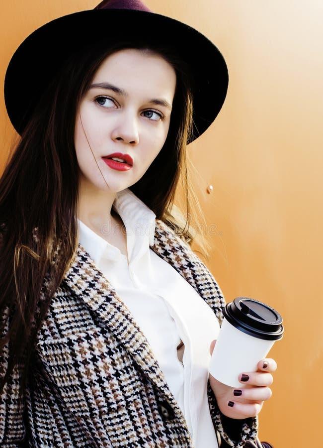 Ung nätt hipsterflickastudent med kaffekoppen som poserar förtjusande le, utomhus- livsstilfolkbegrepp arkivbilder