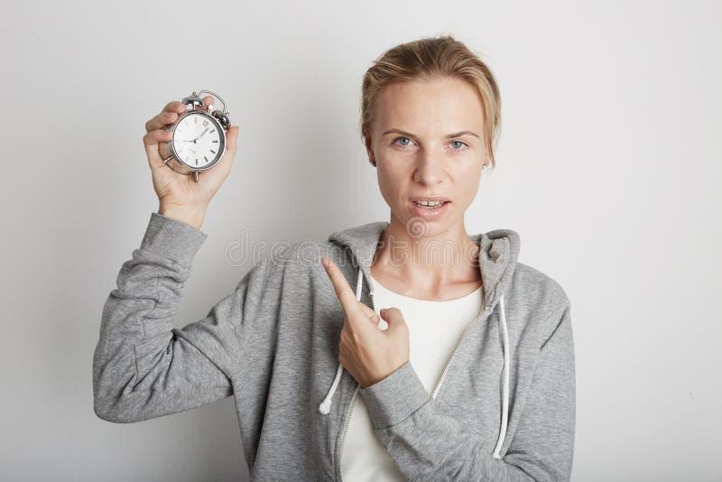 Ung nätt klocka för kvinnainnehavlarm Vit backgroung arkivfoton