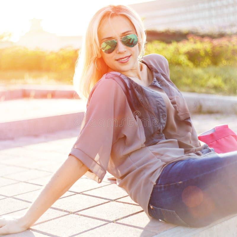 Ung nätt kvinna i solglasögon som sitter på trappa arkivbild