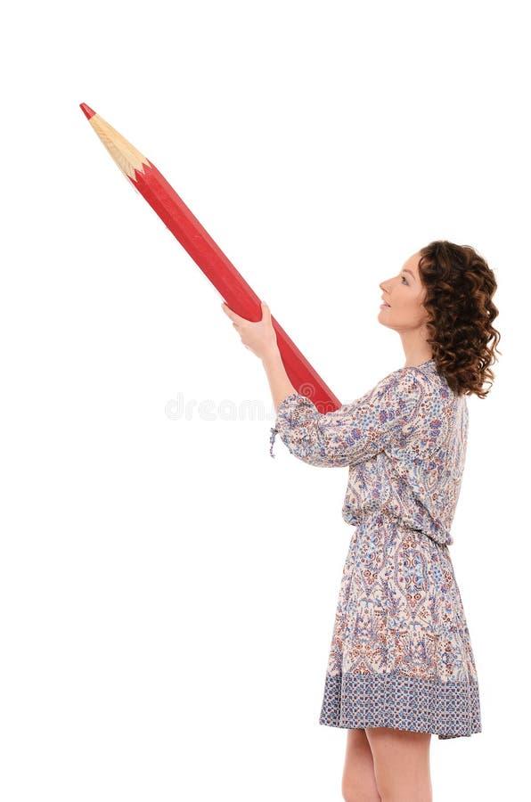 Ung nätt kvinna med den jätte- röda blyertspennan royaltyfria bilder