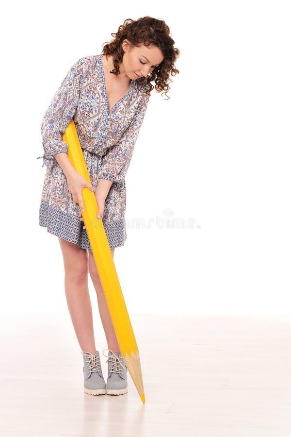 Ung nätt kvinna med den stora gula blyertspennan royaltyfri bild