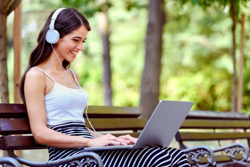 Ung nätt kvinna med hörlurar som sitter på bänk i parkera, genom att använda bärbar datordatoren arkivfoton