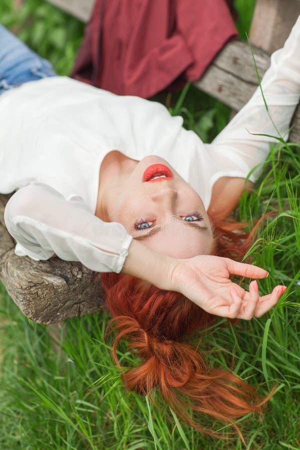 Ung nätt kvinna med rött hår som ligger på trädgårds- koppla av för bänk royaltyfri bild