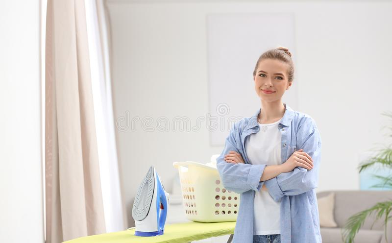 Ung nätt kvinna nära strykbräda med korgen av den rena tvätterit inomhus arkivbild