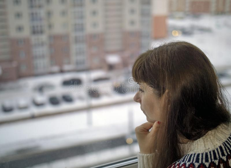 Ung nätt kvinna se som är ledsen ut fönstret till gatan utanför, suddig bakgrund royaltyfri bild