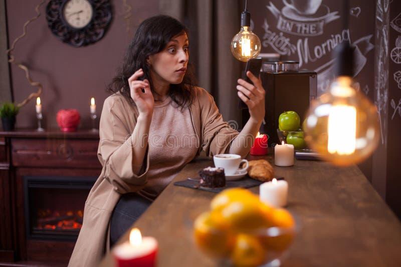 Ung n?tt kvinna som anv?nder mobiltelefonen i en coffee shop och g?r roliga framsidor royaltyfria bilder