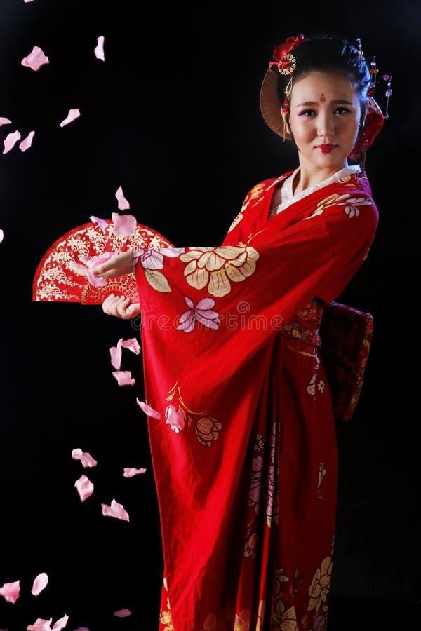 Ung nätt kvinna som bär den röda kimonot royaltyfri foto