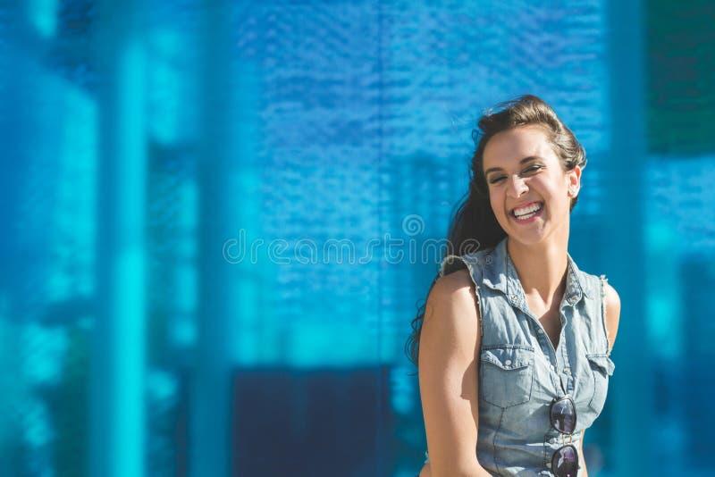 Ung nätt kvinna som grundligt skrattar på blå bakgrund royaltyfria bilder