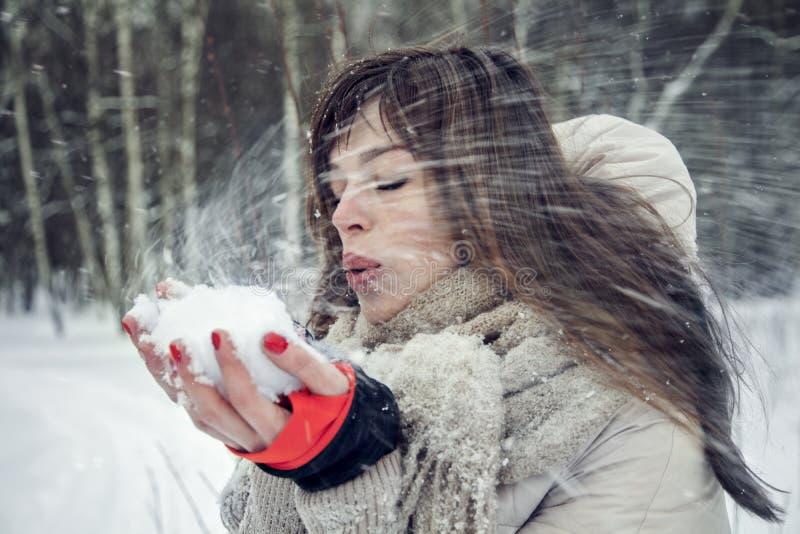 Ung nätt kvinna som har gyckel i vinterskogen i rörelse arkivfoto