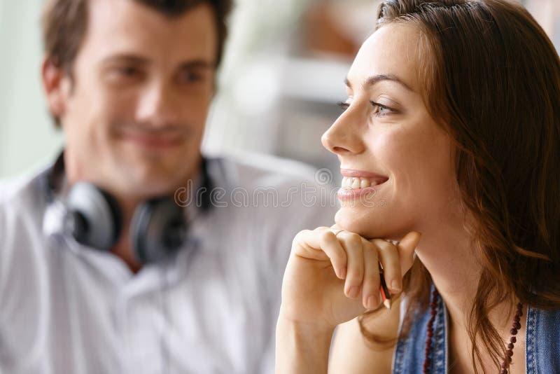 Ung nätt kvinna som ler med mannen på bakgrund royaltyfri foto