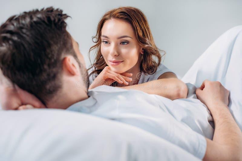 ung nätt kvinna som lutar på pojkvän, medan vila på säng tillsammans fotografering för bildbyråer