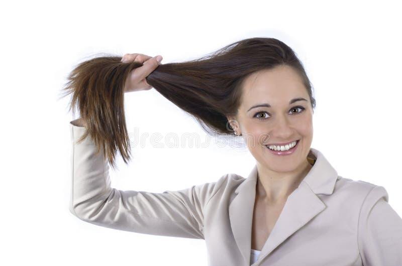 Ung nätt kvinna som rymmer hennes långa hår royaltyfri fotografi